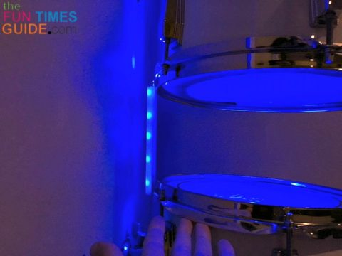A closeup of the cord hider between 2 drums on the wall, with the exposed LED lights facing the wall.