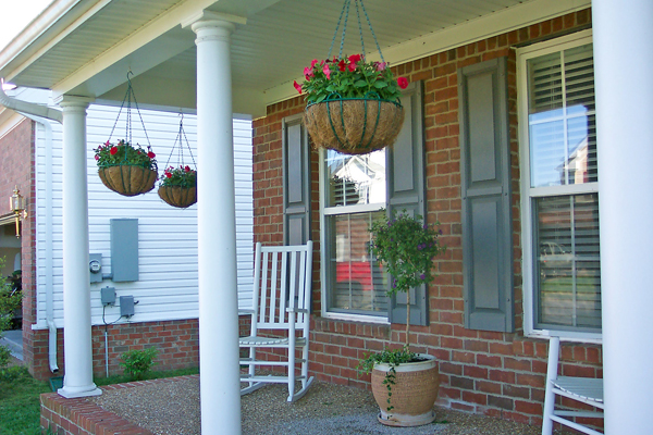 My hanging flower baskets on the front porch filled with red impatiens.