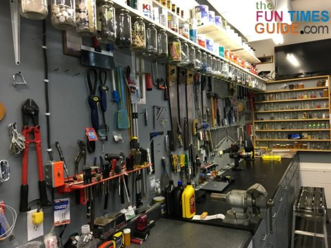 An organized garage workspace with everything in its place and a DIY shelf organizer made from glass jars and lids.