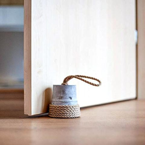A simple but rustic DIY door stop is to use an empty tin can or bucket filled with something heavy and decorated with fabric rope -- like jute or hemp.