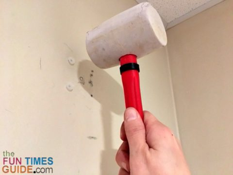 Using a rubber mallet to get the drywall toggle anchors flush with the wall.