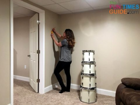 Using a stud finder to locate the stud in the wall and marking where each drum will go.