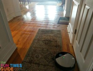 This photo shows how the iLife vacuum travels across the hardwood flooring, carpeting, and rugs -- even though the mop pad and water canister are attached.